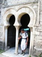 Un peregrino atraviesa la puerta mozárabe de la iglesia de Santiago. 15 agosto 2008. Enrique L. Manzano.