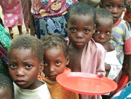Unos niños africanos hacen cola para recibir alimentos.