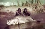 Niños africanos con una carpa del Nilo. 20minutos.es.