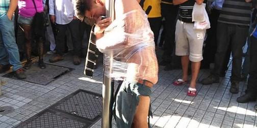 El ladrón fue atado por la gente a la farola con cinta transparente. Santiago de Chile, 28 nov. 2014. Moedetriana.com.